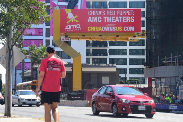 """洛杉矶日落大道上高悬的一块广告牌打出一句标语:""""中共的红色傀儡:AMC剧院""""。(FREDERIC J. BROWN/AFP/Getty Images)"""