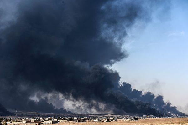图为10月18日,IS分子点燃油井以图阻止伊军的进攻。 ( BULENT KILIC/AFP/Getty Images)
