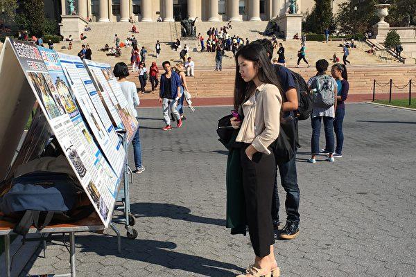 一位华人学生在仔细观看图片展的展板。 (李兰/大纪元)