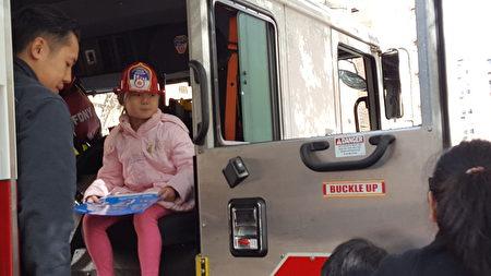 顾雅明举办秋季园游会,孩子戴上消防局赠送的消防员头盔,到消防车上参观。
