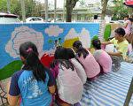 學童利用彌陀國小外牆進行美術創作,用畫筆講述家鄉的故事。(高市海洋局提供)