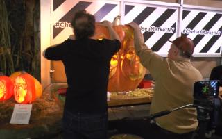 雕刻师正在雕刻川普和希拉里合体的大南瓜灯,旁边2个小的已经完工,唯妙唯肖。 (韩瑞/大纪元)