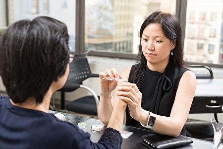 紐約手部職能治療師黃思暖正在仔細看診。(張學慧/大紀元)