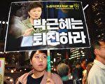 韓國總統樸槿惠今天(2日)宣布改組內閣,撤換總理和兩位內閣首長,以平息因親信門醜聞所犯眾怒。圖為韓國民眾在一場集會中手舉要求樸瑾惠下台的標語。(AFP PHOTO/JUNG YEON-JE)