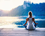 瑜伽蓮花。年輕女子在湖邊做瑜伽,坐在蓮花。(fotolia)