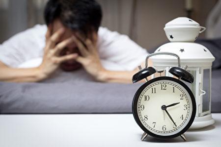 亞洲男子在床上痛苦失眠和睡眠障礙想著他在晚上的問題