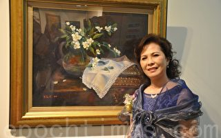 朱美珍理事长和她的油画作品。(李晴玳/大纪元)