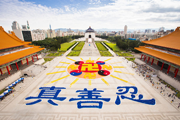 """二零一六年十一月二十六日,台湾部分法轮功学员约六千人,他们身穿着深黄、浅黄、红、黑、蓝、白色的服饰,在中正纪念堂前排出壮观的""""法轮图形""""、十六道光芒及下方文字""""真、善、忍""""。(陈柏州/大纪元)"""