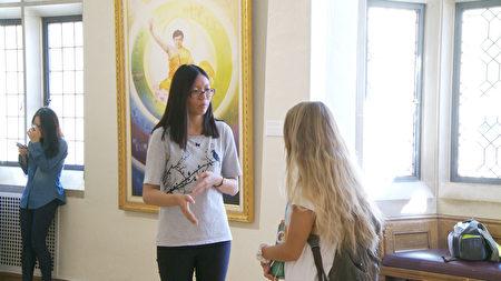 UCLA法輪大法社團的成員Joyce Kuo向Bianca Marcello解釋畫展背景。(楊陽/大紀元)