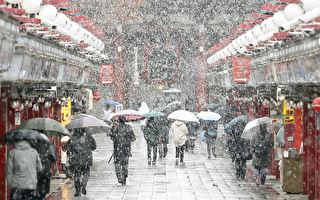 日本東京24日下起雪來,這是東京54年來第一場11月雪 ,民眾冒著寒風走在通往淺草寺的仲見世通商店街上。(共同社提供/中央社)
