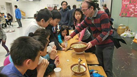 联合中文学校赖飞钟校长,正在给学生派发擂茶。 (邱晨/大纪元)