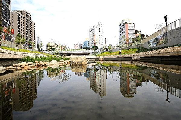 柳川整治工程同時導入LID工法,渠底亂石片鋪列,並使用水撲滿、雨花園、透水鋪面及廣植喬木,地表水可滲透進土壤,打造會呼吸的河川。(台中市政府提供)