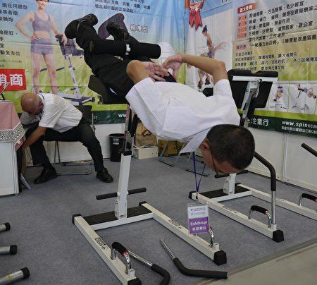 澄村企業展示的倒立機,能幫助倒立、脊柱牽引和肌肉鍛鍊融合一起,達到全方位運動,男女老少皆適宜。(方金媛/大紀元)