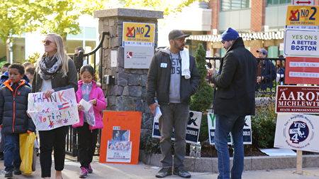 """手拿鼓励投票标语的小朋友在老师带领下,到波士顿""""中国城""""总统大选投票点做""""户外教学""""参访。(贝拉/大纪元)"""