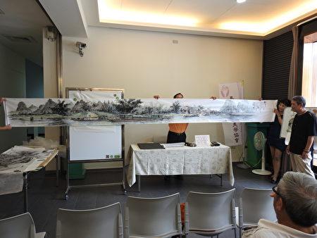 林勋谅老师在美学讲座上,展示他的巨幅创作《桂林漓江游》。(蔡上海/大纪元)