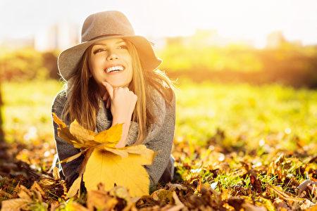 研究顯示,光線的種類與亮度會影響人們的情緒,比如自然光會使人更快樂。圖為一名年輕女子在陽光明媚的秋日公園。(Fotolia)