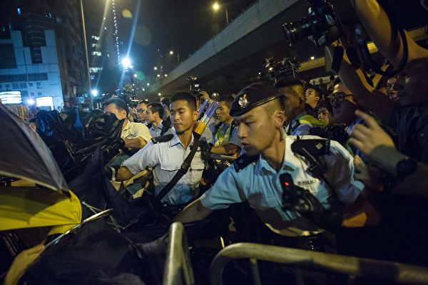 Police use pepper spray to stop protesters charging outside the Chinese Liason Office in Hong Kong on November 6, 2016, during a protest against an expected interpretation of the city's constitution -- the Basic Law -- by China's National People's Congress Standing Committee (NPCSC) over the invalid oath-taking attempts by newly elected lawmakers Baggio Leung and Yau Wai-ching at the Legislative Council last month. Thousands took to Hong Kong's streets on November 6 after Beijing said it would step into an escalating row over whether two city lawmakers who advocate a split from China should be banned from taking up their seats. / AFP / ISAAC LAWRENCE (Photo credit should read ISAAC LAWRENCE/AFP/Getty Images)