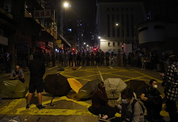Police block off a street as protesters sit with umbrellas amid ongoing protests in Hong Kong on November 6, 2016. Hong Kong police used pepper spray November 6 to drive back hundreds of protesters angry at China's decision to intervene in a row over whether two pro-independence lawmakers should be barred from the city's legislature. In chaotic scenes reminiscent of mass pro-democracy protests in 2014, demonstrators charged metal fences set up by police outside China's liaison office in the semi-autonomous city. / AFP / Anthony WALLACE (Photo credit should read ANTHONY WALLACE/AFP/Getty Images)