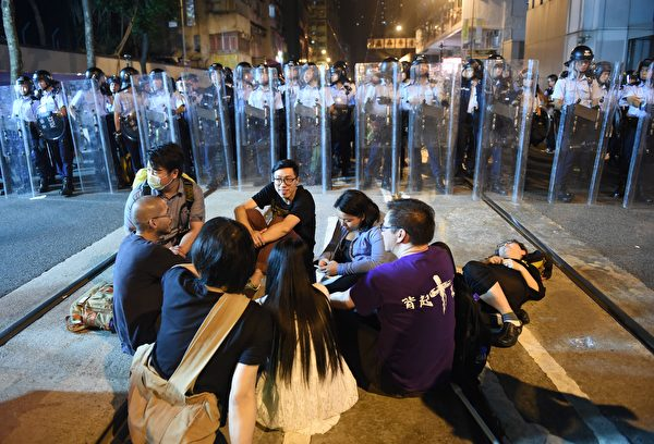 Protesters sit on a main street which has been blocked off as police in riot gear hold shields as they stand guard amid ongoing protests in Hong Kong on November 6, 2016. Hong Kong police used pepper spray November 6 to drive back hundreds of protesters angry at China's decision to intervene in a row over whether two pro-independence lawmakers should be barred from the city's legislature. In chaotic scenes reminiscent of mass pro-democracy protests in 2014, demonstrators charged metal fences set up by police outside China's liaison office in the semi-autonomous city. / AFP / Anthony WALLACE (Photo credit should read ANTHONY WALLACE/AFP/Getty Images)