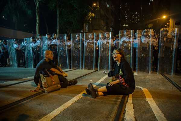 Protesters sit in a road as police in riot gear stand guard amid ongoing demonstrations in Hong Kong on November 6, 2016. Hong Kong police used pepper spray November 6 to drive back hundreds of protesters angry at China's decision to intervene in a row over whether two pro-independence lawmakers should be barred from the city's legislature. In chaotic scenes reminiscent of mass pro-democracy protests in 2014, demonstrators charged metal fences set up by police outside China's liaison office in the semi-autonomous city. / AFP / ISAAC LAWRENCE (Photo credit should read ISAAC LAWRENCE/AFP/Getty Images)