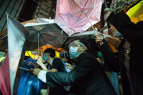 A protester wearing a mask hides behind umbrellas amid ongoing protests and clashed with police in Hong Kong on November 6, 2016. Hong Kong police used pepper spray November 6 to drive back hundreds of protesters angry at China's decision to intervene in a row over whether two pro-independence lawmakers should be barred from the city's legislature. In chaotic scenes reminiscent of mass pro-democracy protests in 2014, demonstrators charged metal fences set up by police outside China's liaison office in the semi-autonomous city. / AFP / ISAAC LAWRENCE (Photo credit should read ISAAC LAWRENCE/AFP/Getty Images)