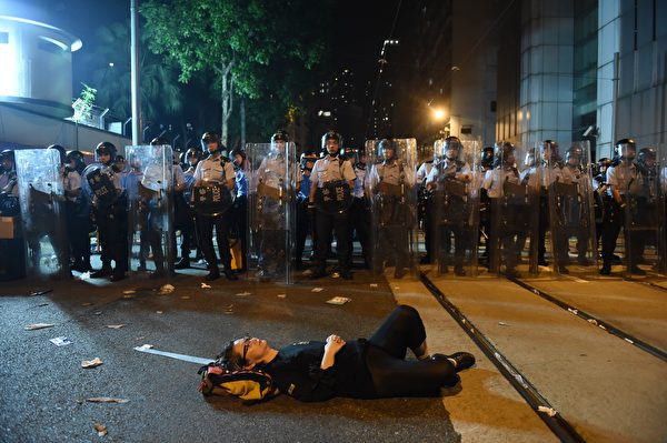 A protesters lies on a blocked street as police in riot gear stand guard amid ongoing protests in Hong Kong on November 6, 2016. Hong Kong police used pepper spray November 6 to drive back hundreds of protesters angry at China's decision to intervene in a row over whether two pro-independence lawmakers should be barred from the city's legislature. In chaotic scenes reminiscent of mass pro-democracy protests in 2014, demonstrators charged metal fences set up by police outside China's liaison office in the semi-autonomous city. / AFP / Anthony WALLACE (Photo credit should read ANTHONY WALLACE/AFP/Getty Images)