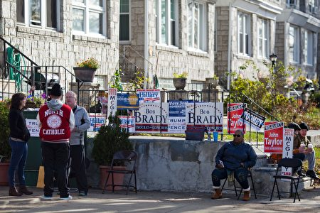 Volunteers wait for voters outside a polling station in Philadelphia, Pennsylvania, on election day November 8, 2016. America's future hung in the balance Tuesday as millions of eager voters cast ballots to elect Democrat Hillary Clinton as their first woman president, or hand power to the billionaire populist Donald Trump. As the world held its collective breath, Americans were called to make a historic choice between two radically different visions for the most powerful nation on Earth. / AFP / DOMINICK REUTER (Photo credit should read DOMINICK REUTER/AFP/Getty Images)