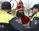 上周六在荷兰Maassluis的圣尼古拉节日欢庆中,警方正在与一名反对黑皮特的人士对话。(LEX VAN LIESHOUT/AFP/Getty Images)