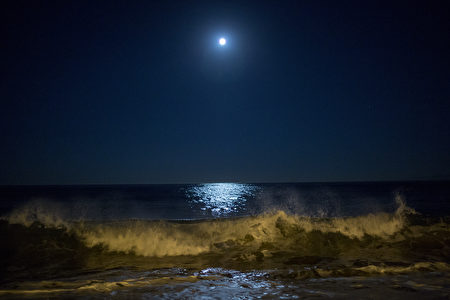 REDONDO BEACH, CA - NOVEMBER 14: Surf breaks as the moon makes its closest orbit to the Earth since 1948 on November 14, 2016 in Redondo Beach, California. The so-called supermoon appears up to 14 percent bigger and 30 percent brighter as it comes about 22,000 miles closer to the Earth than average, though to the casual observer, the increase appears slight. (Photo by David McNew/Getty Images)
