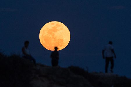 """People watch the supermoon rising in Dar es Salaam on November 14, 2016. The moon will be the closest to Earth since 1948 at a distance of 356,509 kilometres (221,524 miles), creating what NASA described as """"an extra-supermoon"""". / AFP / DANIEL HAYDUK (Photo credit should read DANIEL HAYDUK/AFP/Getty Images)"""