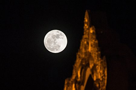 """The """"supermoon"""" rises over Swe Taw Myat Pagoda in Yangon on November 14, 2016 as Myanmar celebrates Tazaungdine festival, a mainly religious celebration coinciding with the appearance of super full moon. Skygazers headed to high-rise buildings, ancient forts and beaches on November 14 to witness the closest """"supermoon"""" to Earth in almost seven decades, hoping for dramatic photos and spectacular surf. The moon will be the closest to Earth since 1948 at a distance of 356,509 kilometres (221,524 miles), creating what NASA described as """"an extra-supermoon"""". / AFP / ROMEO GACAD (Photo credit should read ROMEO GACAD/AFP/Getty Images)"""