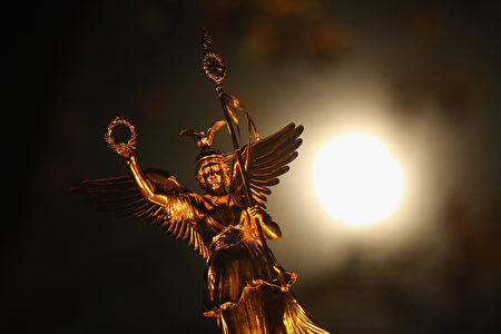 """BERLIN, GERMANY - NOVEMBER 14: The statue of Victoria stands on the Victory Column as the so-called """"super moon"""" is visible behind on November 14, 2016 in Munich, Germany. The """"super moon"""" is a full moon that is at its closest in its elliptical orbit around the Earth, a confluence that last occurred 70 years ago. (Photo by Sean Gallup/Getty Images)"""