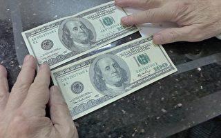 鄧學源昨天拿著100美元假鈔給聯成公所顧問趙文笙看,假鈔(下)對比真鈔,仿真度很高。 (蔡溶/大紀元)