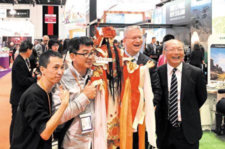 英國國會議員Andrew Rosindell M.P.(右二)手持創意布袋戲偶(天官)與三昧堂創始嚴仁鴻先生(左二)等代表人合影。(主辦方提供)