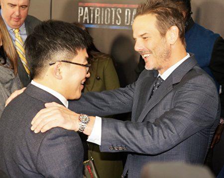 《愛國者日》導演伯格(右)問候波馬爆炸案遭劫車華裔倖存者孟丹尼。(貝拉/大紀元)