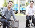 """张宪良(左)以自行开发""""电动义肢手""""骑脚踏车。(云嘉南分署提供)"""