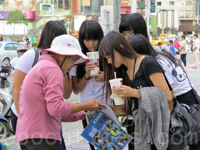 Taiwanese women sign the petition supporting the prosecution of Jiang Zemin. (Li Qingdai/Epoch Times)
