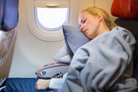 Tired blonde casual caucasian lady napping on uncomfortable seat while traveling by airplane. Commercial transportation by plane