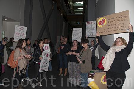 12月24日,旧金山市立大学会议被抗议者打断,图为抗议者在进入会场前展示抗议标牌。(周凤临/大纪元)