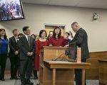 由前副市长曹业云(右)主持,高叙加在父母和义工的见证下,宣誓就任菲利蒙市长。(曹景哲/大纪元)
