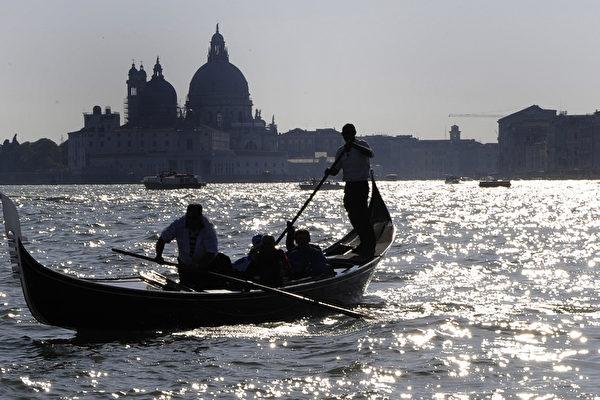 意大利威尼斯,搭乘贡多拉的游客。(DAMIEN MEYER/AFP)