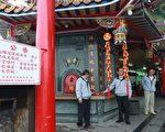 四結福德廟主任委員高志肇(中)示範電子式「環保鞭炮」。左為禁止燃放高空煙火的公告牌。(曾漢東/大紀元)