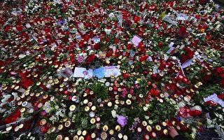 柏林發生恐襲(12月19日)幾天後,位於威廉紀念教堂旁的聖誕市場重新開放,許多民眾來到此地獻上蠟燭、鮮花和卡片,以悼念受害者。(JOHN MACDOUGALL/AFP/Getty Images)