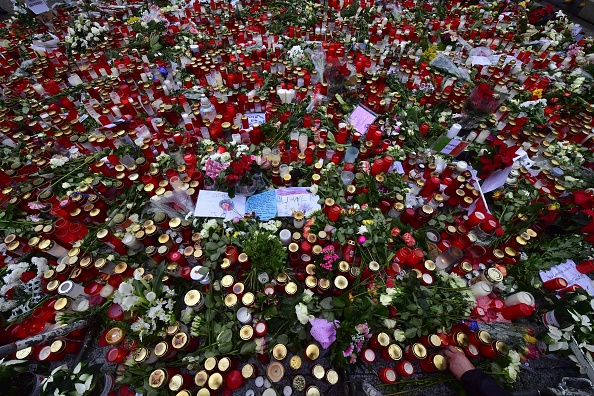 柏林发生恐袭(12月19日)几天后,位于威廉纪念教堂旁的圣诞市场重新开放,许多民众来到此地献上蜡烛、鲜花和卡片,以悼念受害者。(JOHN MACDOUGALL/AFP/Getty Images)