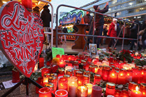 BERLIN, GERMANY - DECEMBER 22: Visitors walk past a makeshift memorial at the reopened Breitscheidplatz Christmas market only a short distance from where three days ago a truck plowed into the market, killed 12 people and injured dozens in a terrorist attack on December 22, 2016 in Berlin, Germany. The Breidscheidplatz Christmas market is reopening today, though its small amusement rides and bright lights displays will remain shut off in a sign of continuing mourning for the attack victims. Meanwhile police have launched a European-wide manhunt for Anis Amri, a 24-year-old Tunisian man they suspect of having driven the truck. (Photo by Sean Gallup/Getty Images)