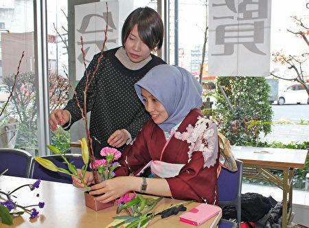 日本廣島市留學生會館於12月17日為留學生主辦「日本文化博覽會」。圖為留學生在體驗插花。(曉玥/大紀元)