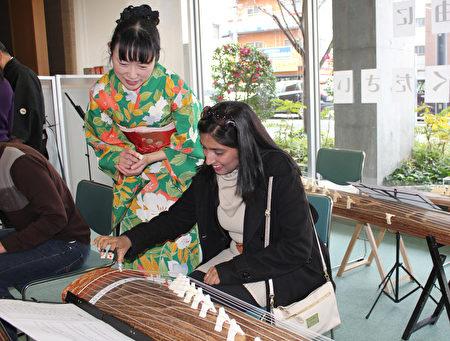 日本廣島市留學生會館於12月17日為留學生主辦「日本文化博覽會」。圖為留學生體驗古箏。(曉玥/大紀元)
