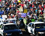 图为2012年1月2日加州帕萨迪纳玫瑰游行期间,警车行进在抗议示威人群的前列。  (FREDERIC J. BROWN/AFP/Getty Images)