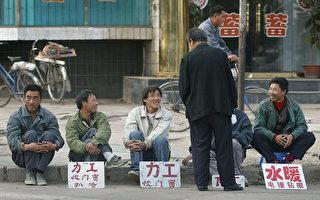 2002年10月辽阳,国企下岗工人坐在路边,等待就业机会。 (FREDERIC J. BROWN/AFP/Getty Images)