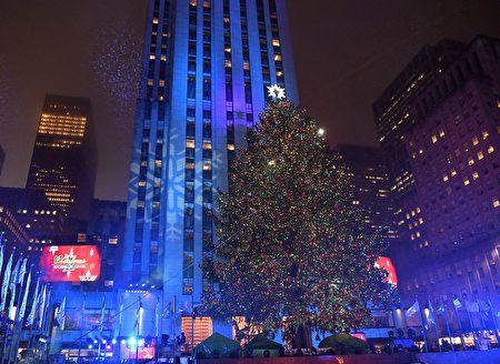 11月30日晚,成千上万的人冒雨齐聚曼哈顿市中心,观赏纽约洛克斐勒中心一年一度的圣诞树点灯仪式。(ANGELA WEISS/AFP/Getty Images)